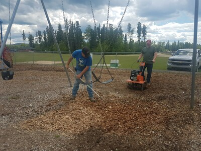 Directors Mike Trithart and Brian Munday work on fluffing up the playground woodchips.
